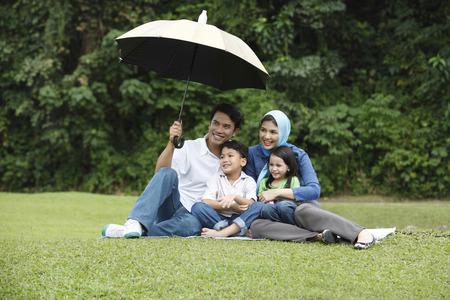 man holding umbrella for his family Standard-Bild