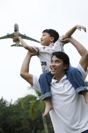 son holding aeroplane sitting on father shoulder