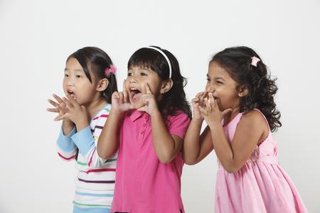 Vista laterale di tre ragazze che gridano insieme