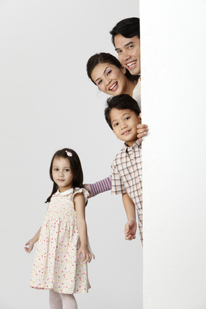 stock image of happy family behind white board