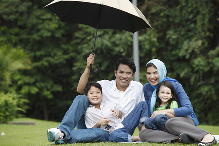 man holding umbrella for his family Imagens