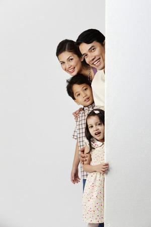 famille se cachant derrière un énorme tableau Banque d'images