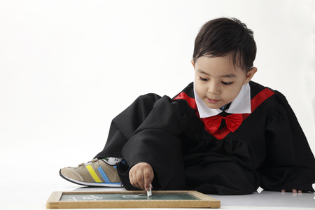 stock image of the boy wearing graduation gown drawing