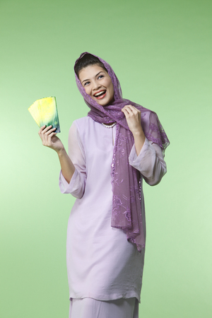happy malay woman wearing baju kurung