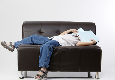 boy covered with book and sleep