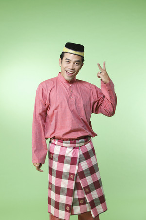 malay man with traditional costume with hand gesture two