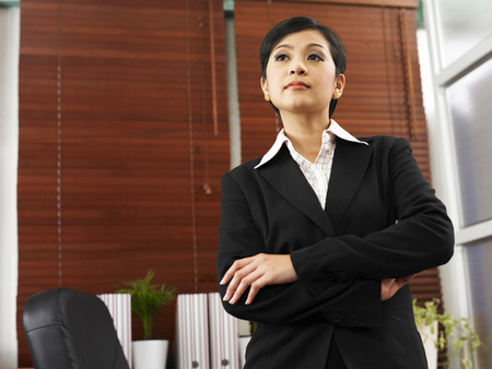 businesswoman with arm crossed standing in her office Stock Photo - 119154085