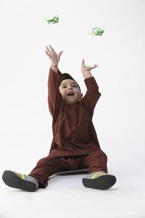 malay boy playing decorative ketupat