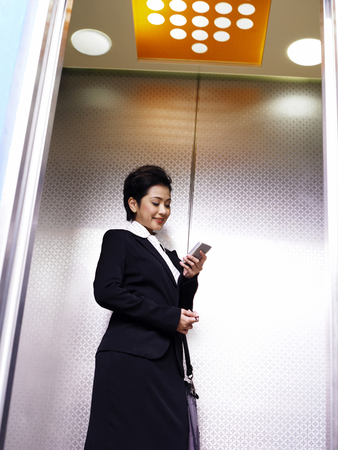 Businesswoman talking on the phone in the elevator