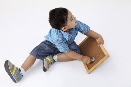 top view  of the boy drawing at small blackboard