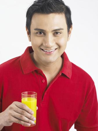 smiling man holding a glass of orange juice Stock Photo