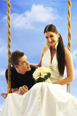 Groom looking at bride sitting on swing, smiling Stock Photo
