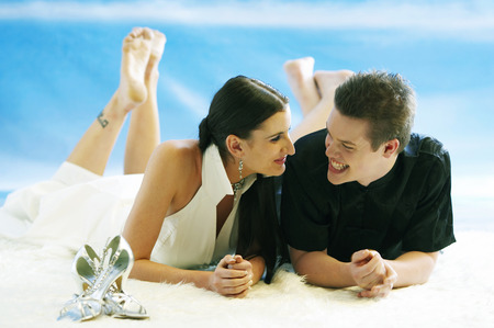 A newly wed couple lying on stomach with crossed legs