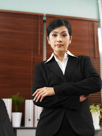 businesswoman in her office with arms crossed