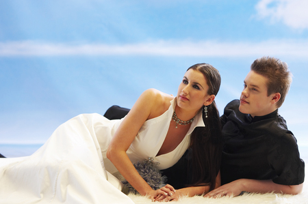 A groom and bride lying on elbow, looking away