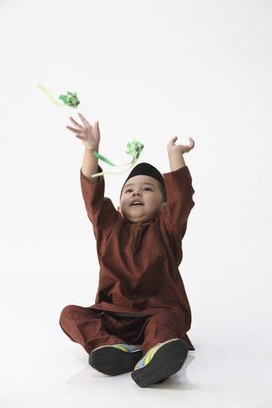 malay boy playing decoration ketupat on the white background