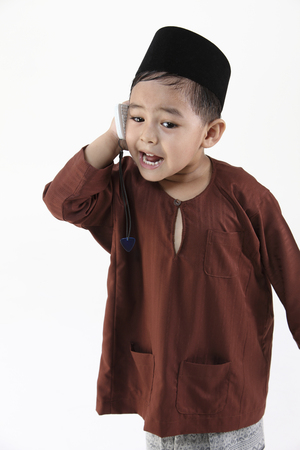 malay boy shouting on the phone Imagens