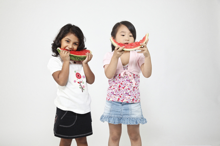 Two girls enjoy eating watermelon Stock Photo