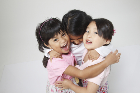 Portrait of three little girls hugging each others
