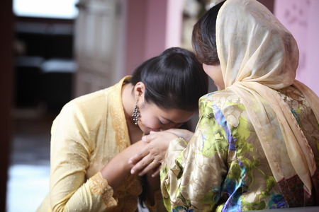 Daughter shake hand with mother and kissing her mother arms