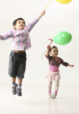 kid holding balloon and jumping together