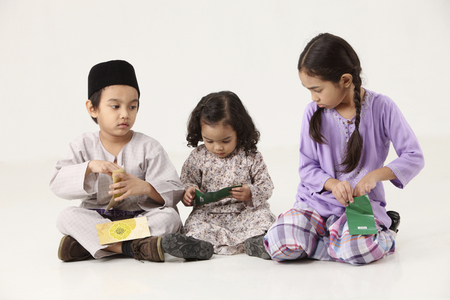 kids opening  green packet Stock Photo