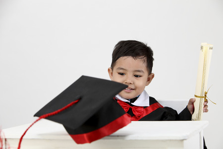 stock image of the boy wearing graduation gown and holding a diploma 免版税图像