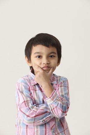Portret van jongen met handen die op de wangen rusten Stockfoto