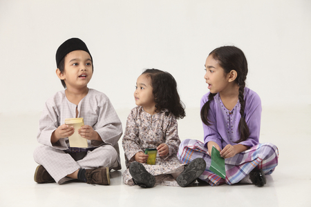 sisters and brother sitting in a row holding a green packet