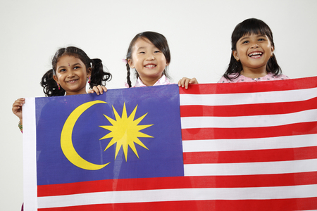 Three girls in traditional costumes holding Malaysia flag