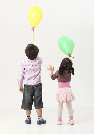 back view of kids holding ballon upward