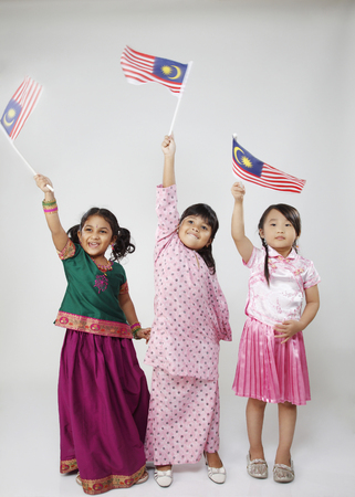 Full lenght of three kids holding flag