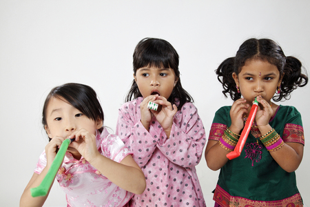 Three kids playing with horn blowers