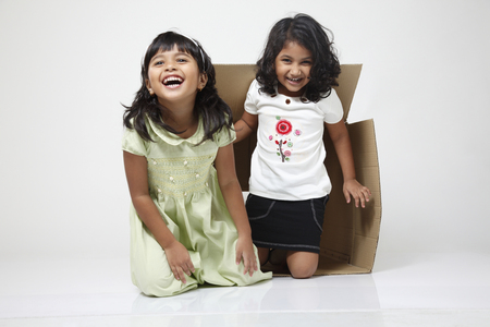 Two little girls coming out from the box