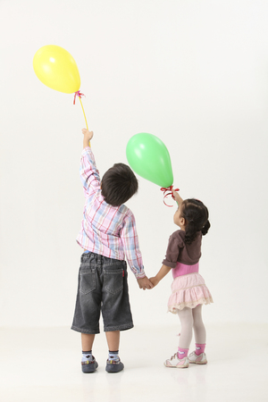 back view of kids holding ballon pointing Stock Photo