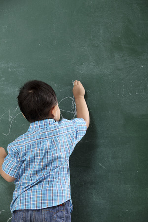 stock image of the malay boy writing on the board
