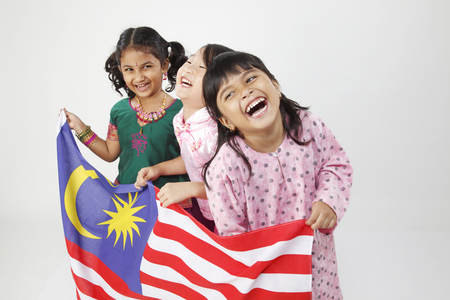 Three girls holding flag, laughing Stock Photo