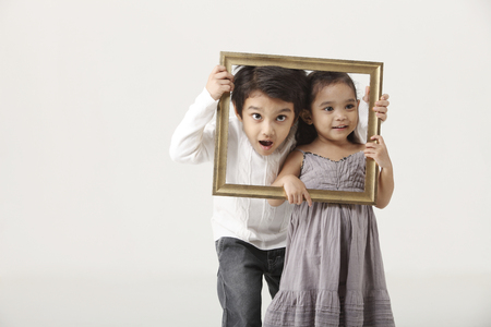 Two kids holding a picture frame