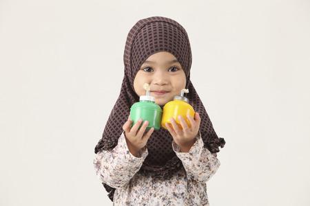 young Muslim Malaysian girl holding pelita looking at camera Stock Photo