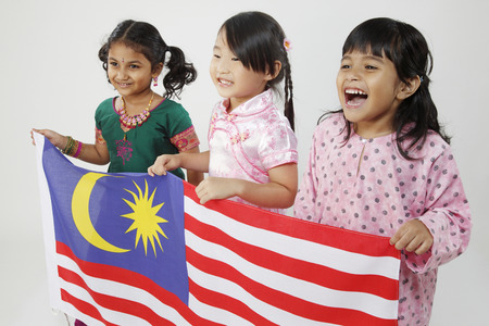 Side view of three girls holding Malaysia flag
