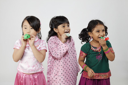 Little girls blowing party horn blower Stock Photo
