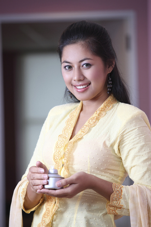 Malay woman holding oil lamp while smiling at camera 免版税图像