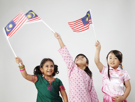 Cropped image of three girls in traditional costume holding flag