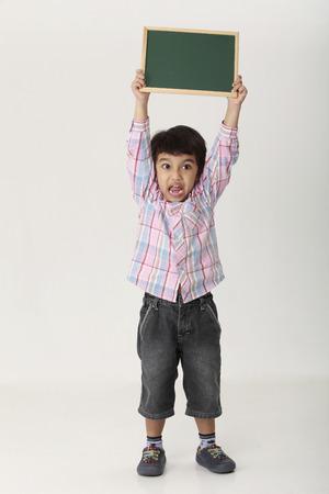 boy holding a blank black board