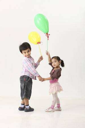 kids holding balloon and look back to camera
