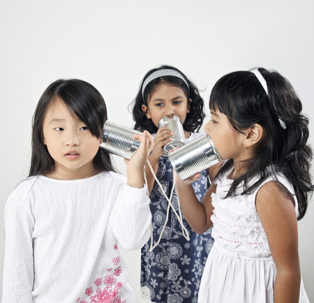 Three girls playing with tin can can phones, talking to each others 版權商用圖片