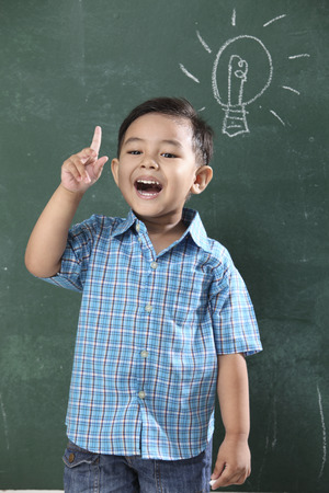 malay boy standing in front of the blackboard with light bulb drawing