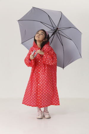 Girl in red raincoat holding umbrella and looking up Stok Fotoğraf