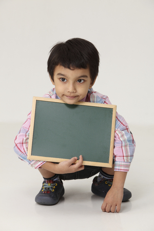 boy squat and holding a blank blackboard
