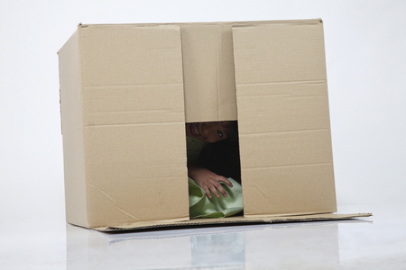 Little girl hiding inside box